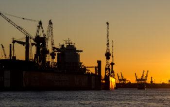 Kräne im Hamburger Hafen bei Sonnenuntergang im Panorama