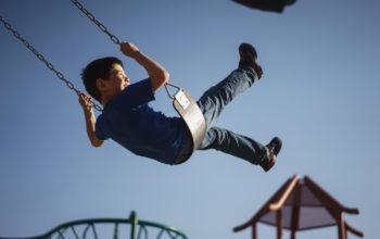 ein Junge schaukelt vor blauem Himmel