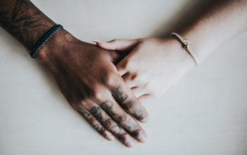 eine dunkel- und eine hellhäutige Hand greifen ineinander